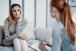 Cocaine Addiction Treatment, A young woman sits on a couch looking at her therapist. She sits up with her legs crossed, one arm and hand resting on her knee and her left elbow rests on her knee also but her left hand is pressed up against her left temple of her forehead. The therapist sits with her back to the camera looking at the young woman while she takes notes from the conversation.