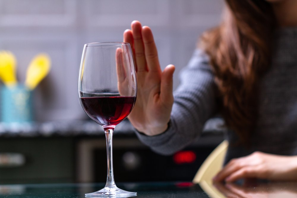 Abstinence - A woman puts her hand up to say no to a glass of wine.