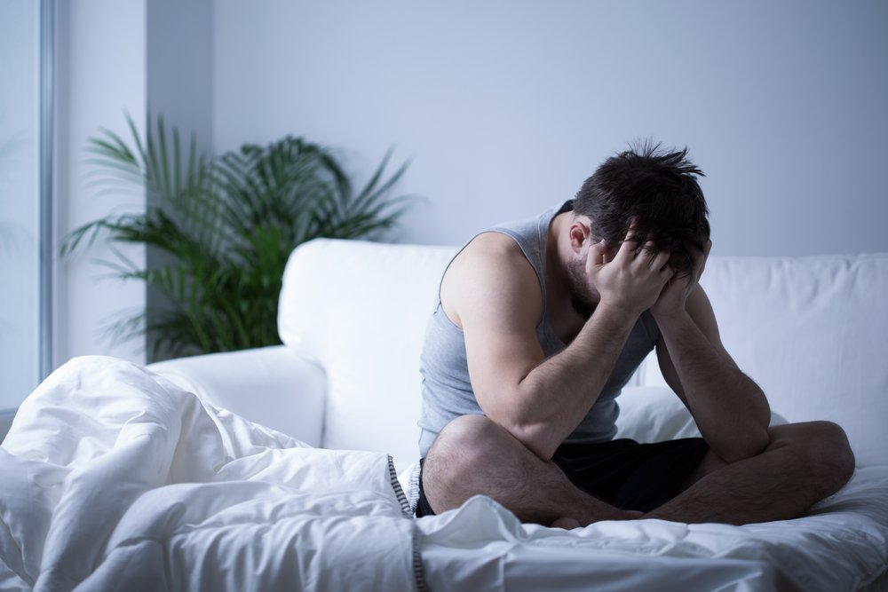 Drugs - A man sits up on his couch with his head in his hands as he is detoxing from drugs.