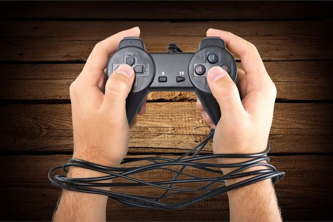 Illustration of online gaming addiction, as shown by hands holding controller with cord wrapped around like handcuffs