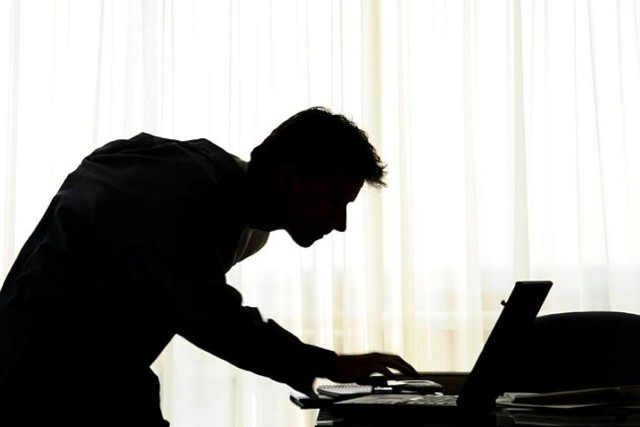 Silhoutte of man at a laptop and with various electronic devices shows the dangers of porn addiction